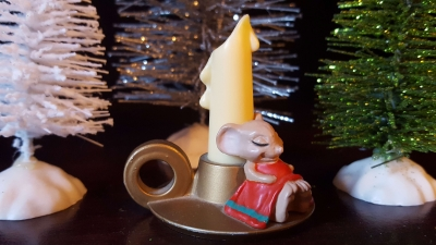 Little mouse sleeping near a candlestick