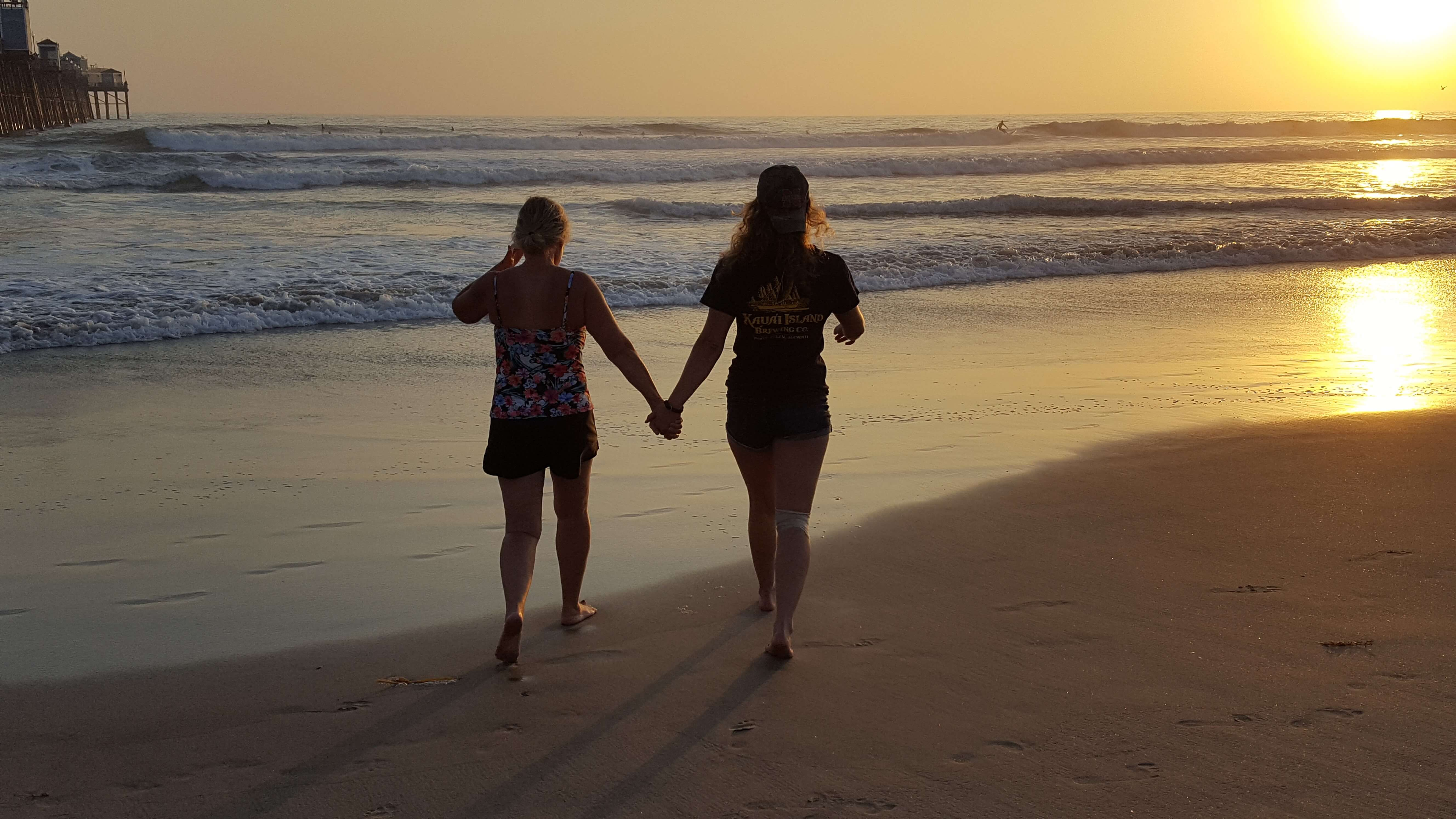 Mom and daughter walking on the beach at sunset
